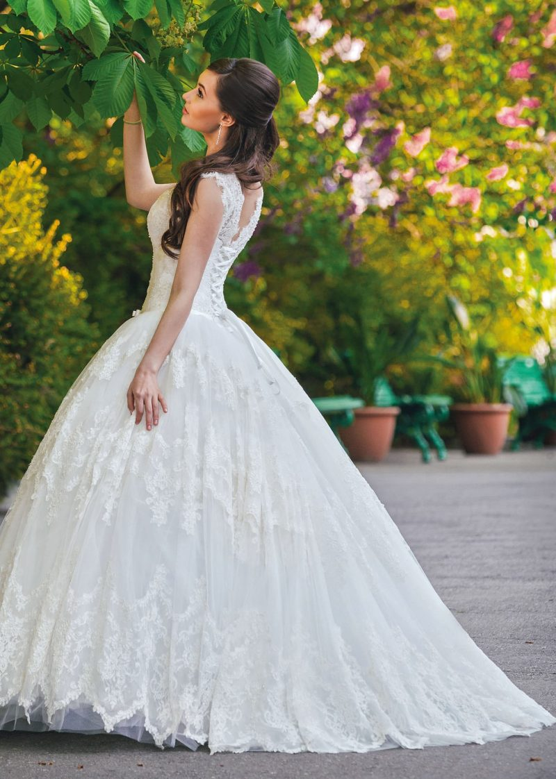 Пышное свадебное платье с отделкой плотным кружевом и V-образным вырезом на спинке.
