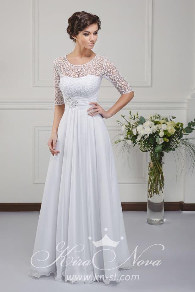 Прямое свадебное платье с вертикальными складками ткани по подолу и рукавом до локтя.