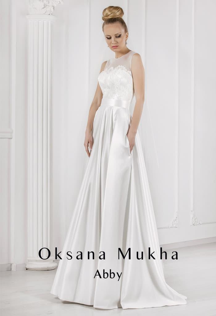 Изысканное свадебное платье с атласной юбкой и полупрозрачной вставкой над лифом.