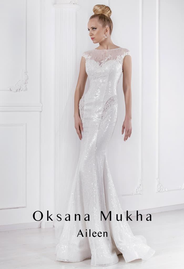 Сияющее свадебное платье облегающего кроя с изящным закрытым лифом и тонкой вставкой сзади.