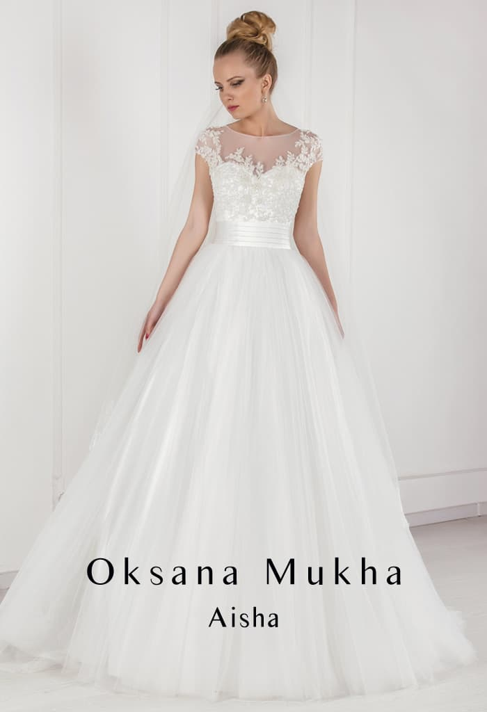 Пышное свадебное платье с кружевным лифом и широким поясом из атласной ткани.