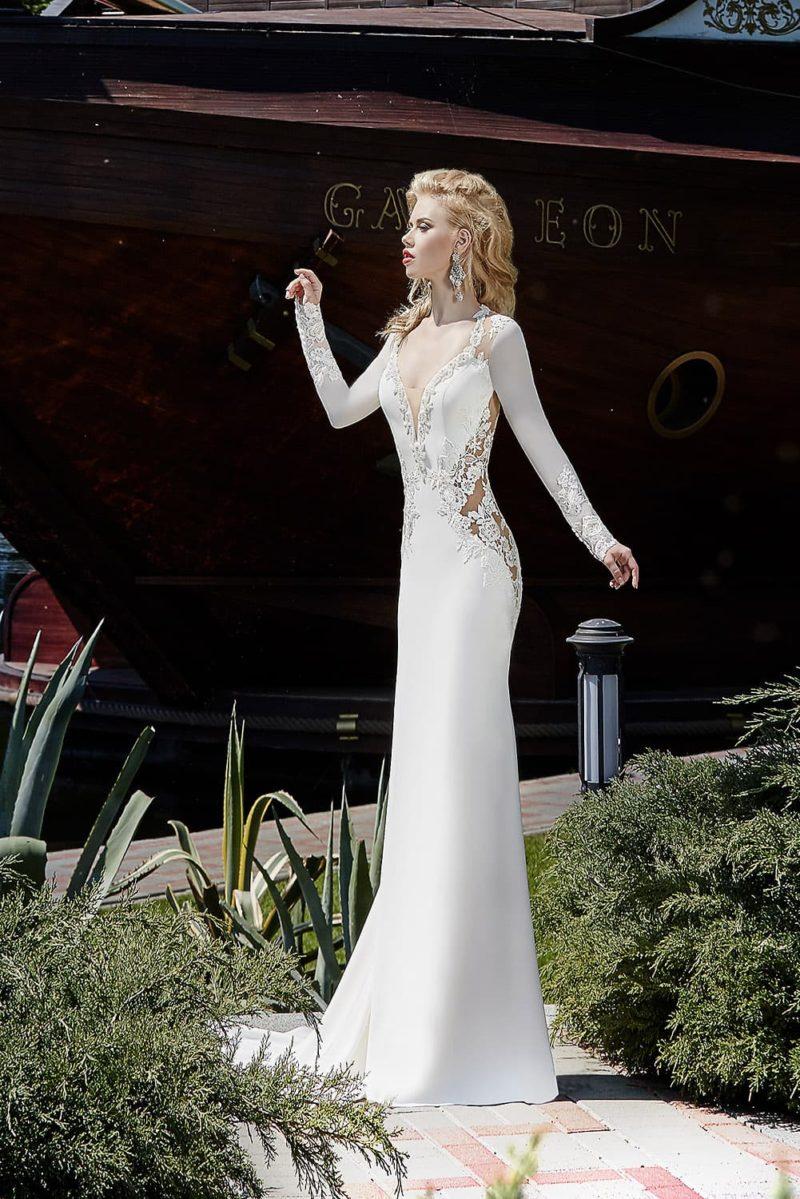 Прямое свадебное платье с кружевными вставками по бокам корсета, длинным рукавом и стильным шлейфом.