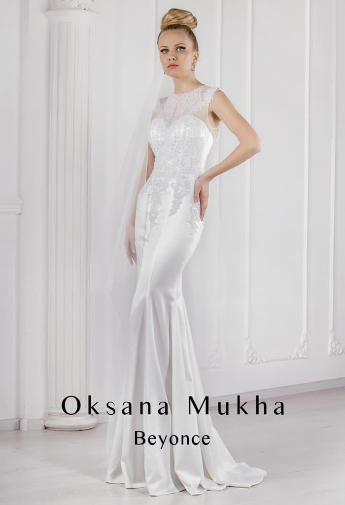 Атласное свадебное платье облегающего кроя с закрытым верхом без рукавов.