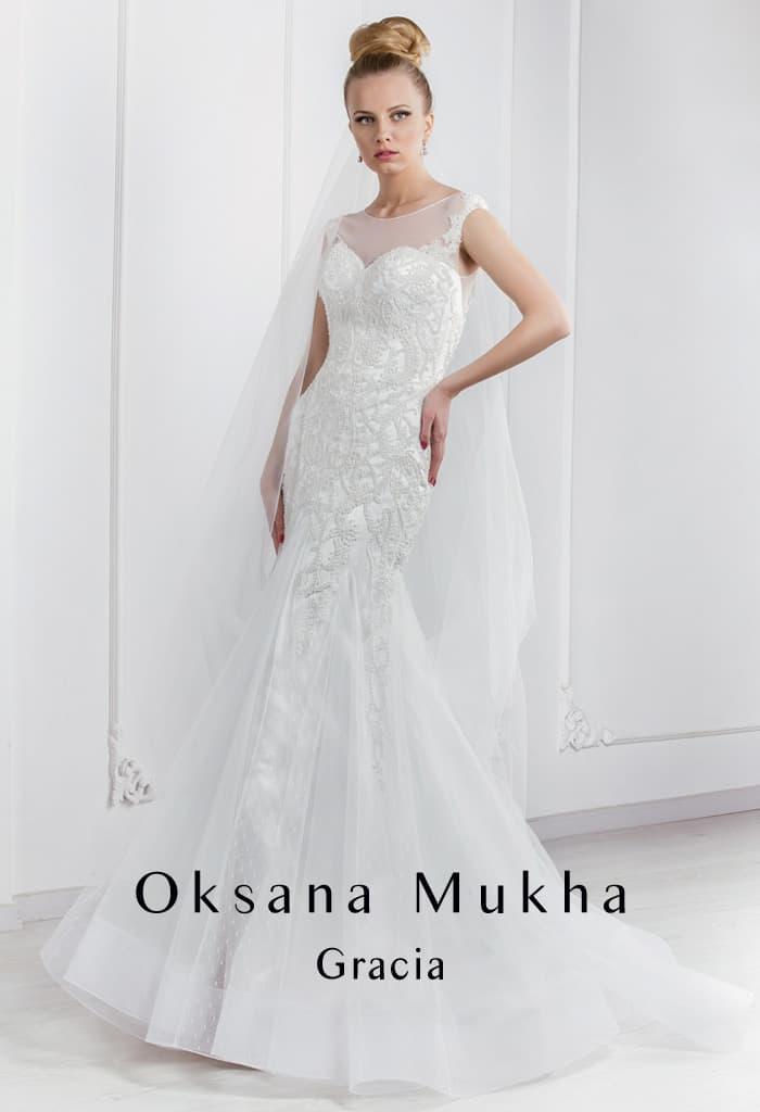 Облегающее свадебное платье с полупрозрачной вставкой над декольте и вышивкой по корсету.