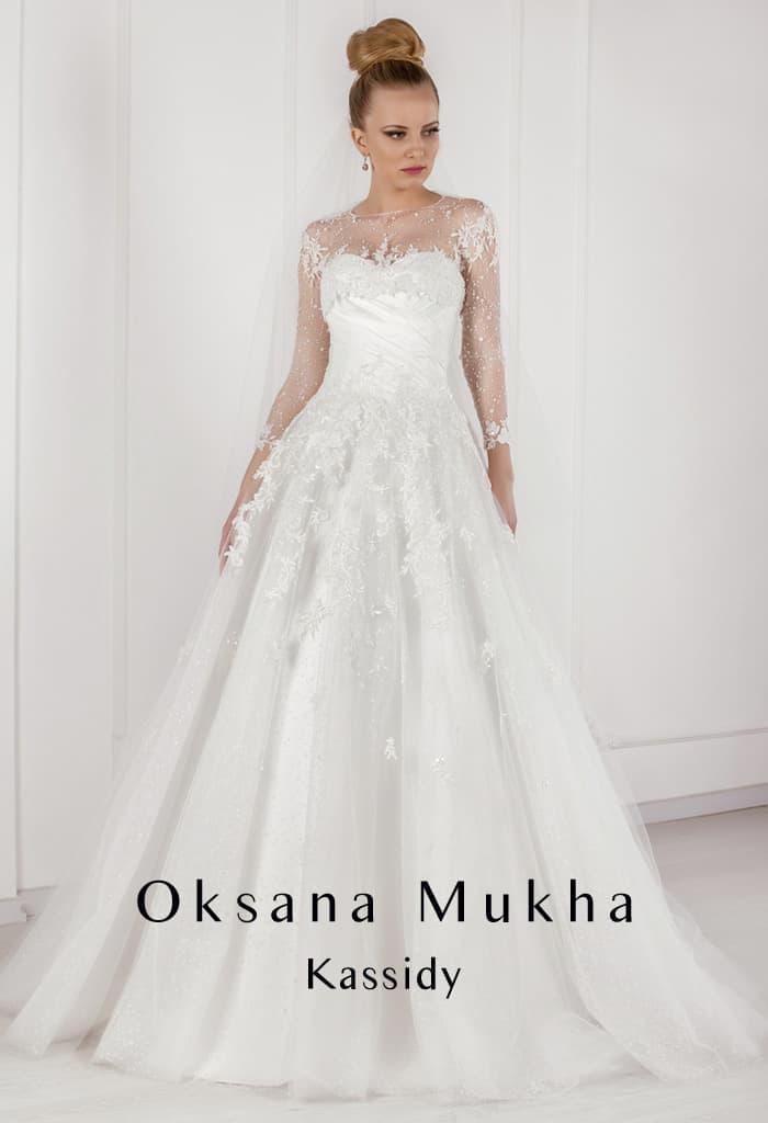 Утонченное свадебное платье пышного кроя с полупрозрачными рукавами.