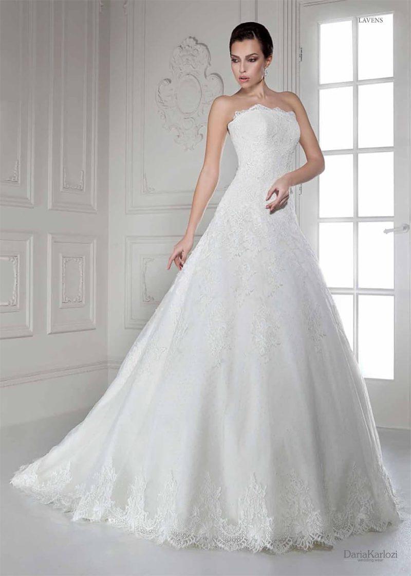 Нежное свадебное платье традиционного кроя с открытым лифом и кружевом по подолу.