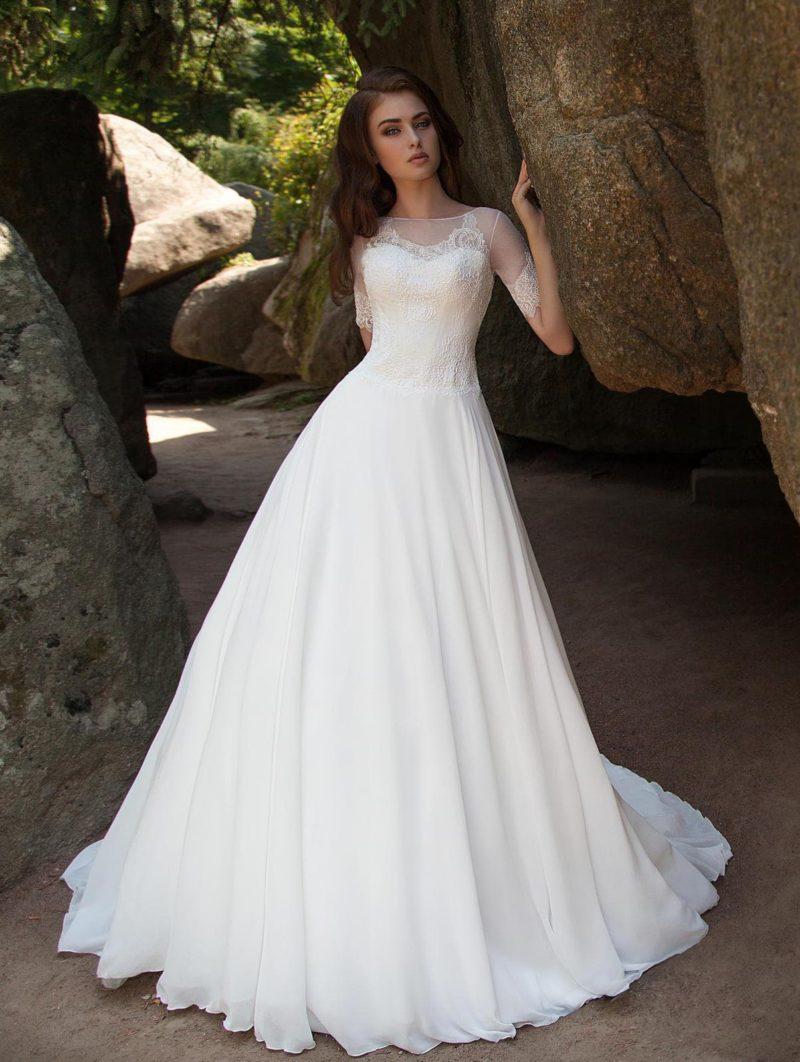 Пышное свадебное платье с женственным закрытым верхом с округлым вырезом.