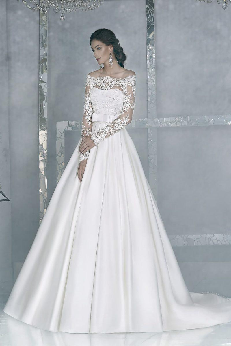 Атласное свадебное платье элегантного кроя с портретным декольте и изящным шлейфом сзади.