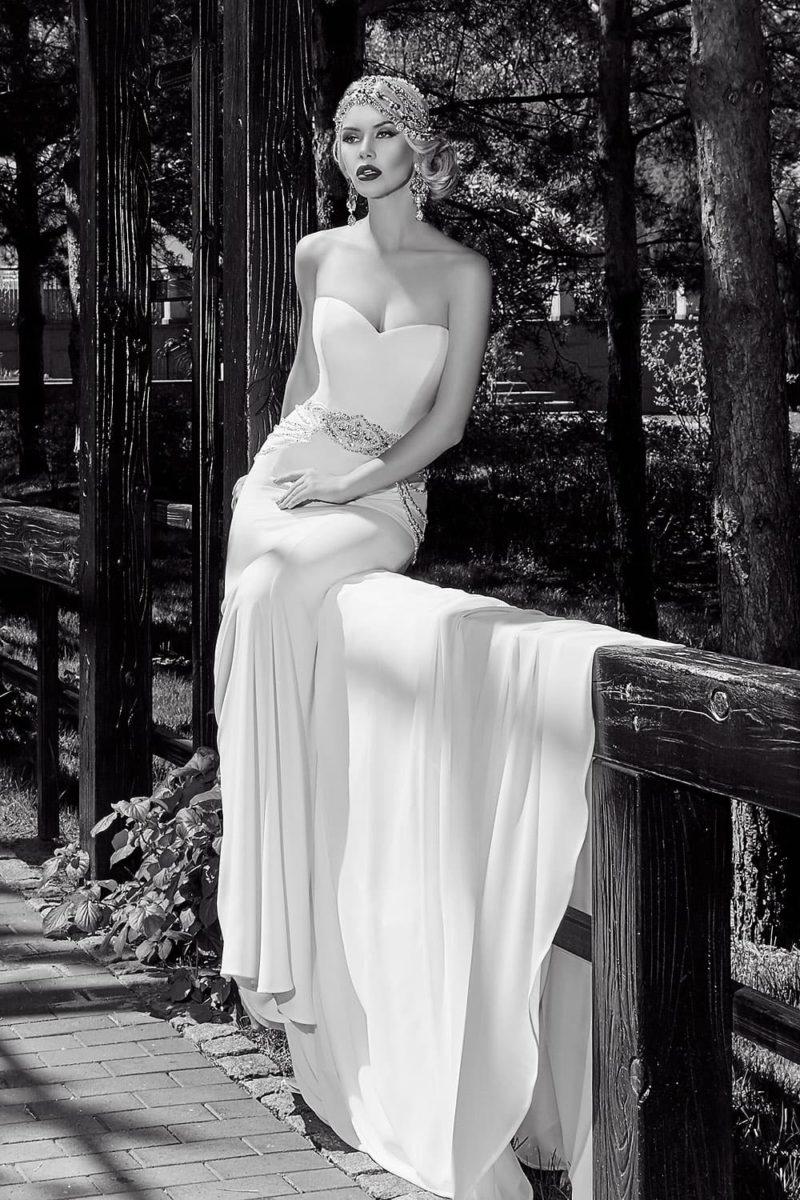 Свадебное платье прямого кроя с широким поясом, украшенным бисерной отделкой.