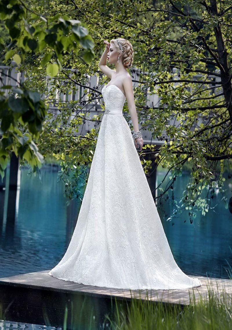 Роскошное свадебное платье из фактурной ткани, с широким поясом и дополнительным шлейфом.