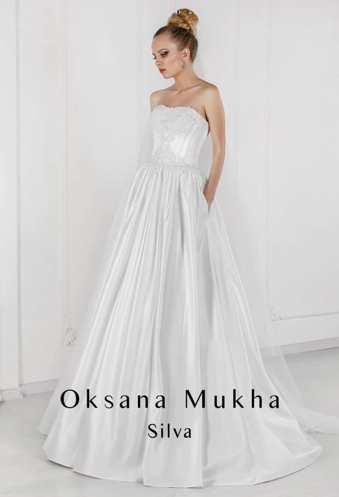Атласное свадебное платье с открытым верхом и скрытыми карманами на юбке.