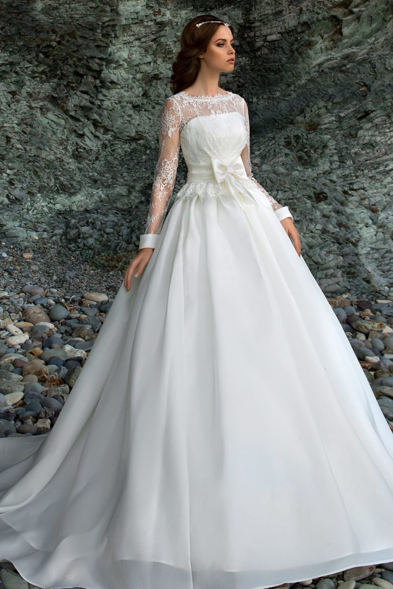 Свадебное платье с кружевной баской, поясом с бантом и многослойной торжественной юбкой.