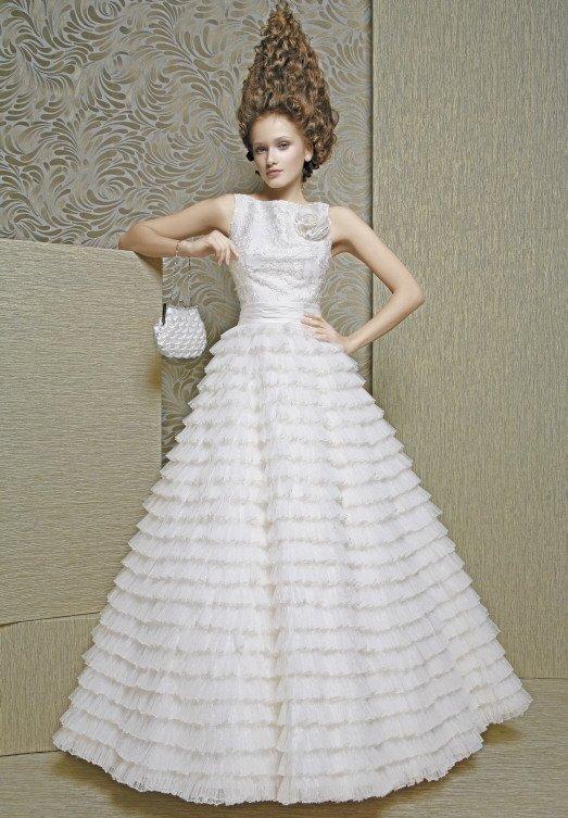 Свадебное платье с множеством оборок по пышной юбке и закрытым лифом.