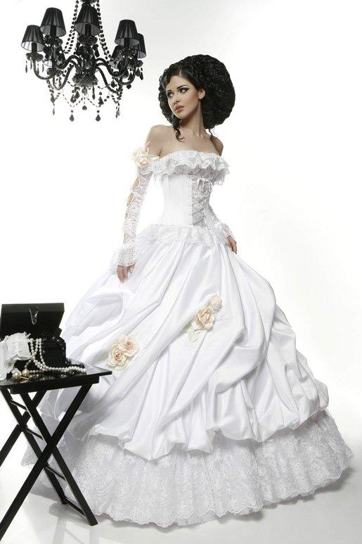 Драматичное свадебное платье с отделкой кремовыми бутонами и портретным декольте.