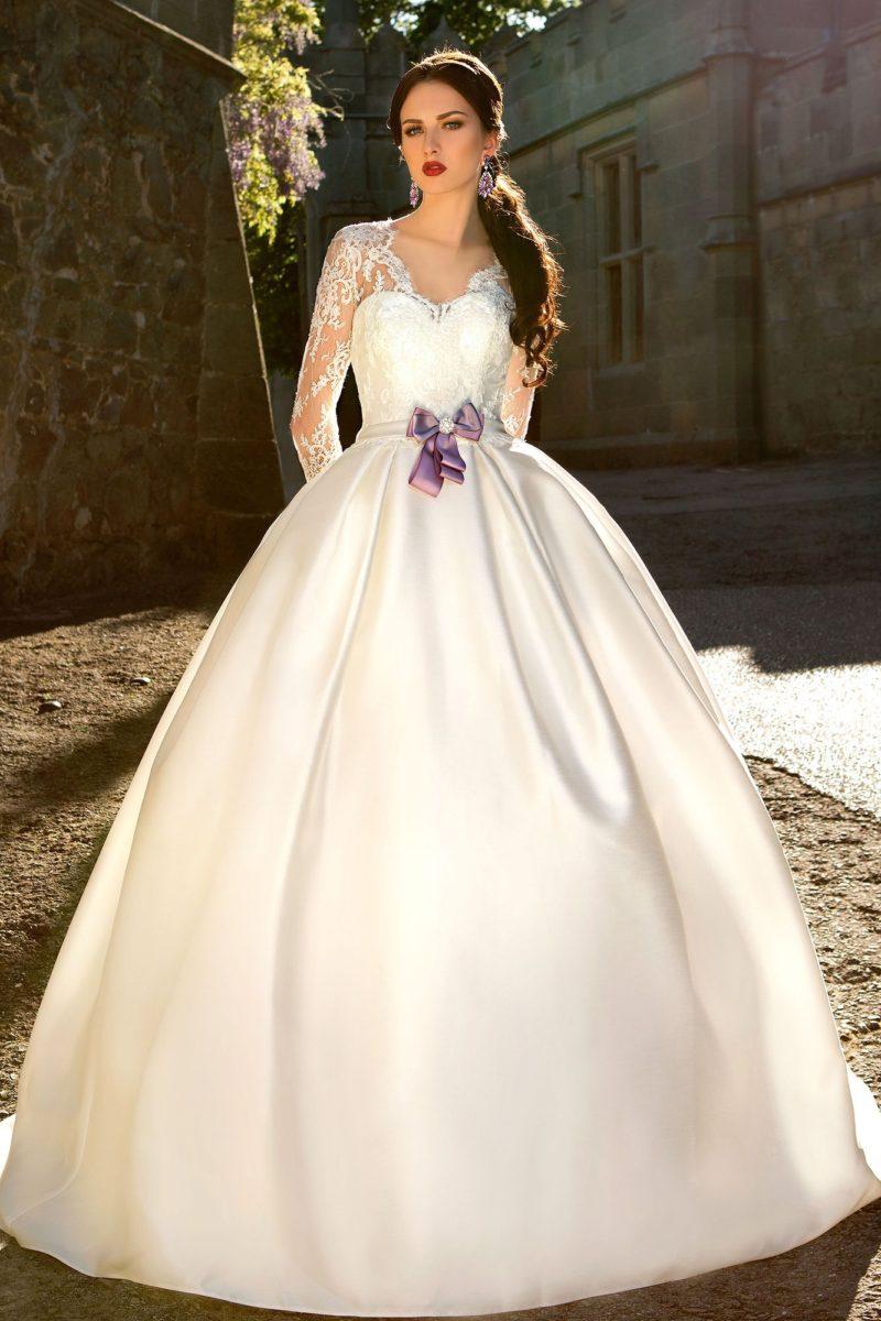Атласное свадебное платье с длинными кружевными рукавами и лиловым поясом с бантом.
