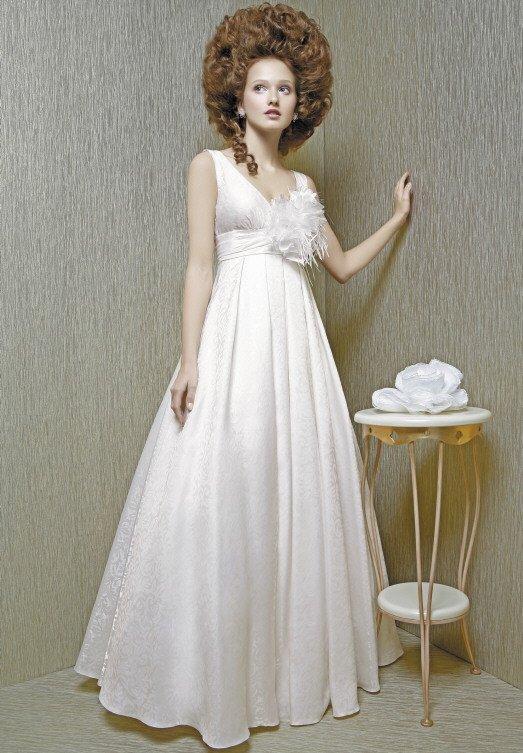 Фактурное свадебное платье А-силуэта с завышенной талией и бутоном на лифе.