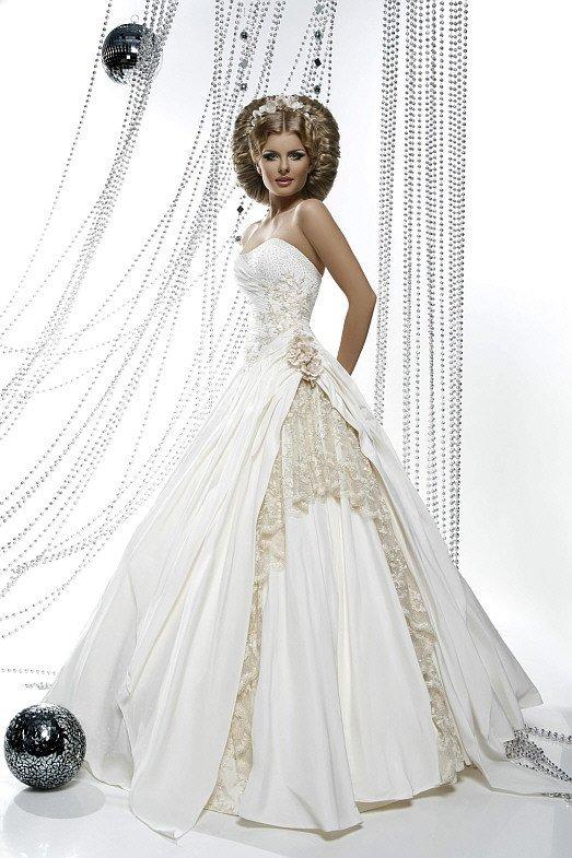 Открытое свадебное платье пышного кроя, оформленное золотистым кружевом.