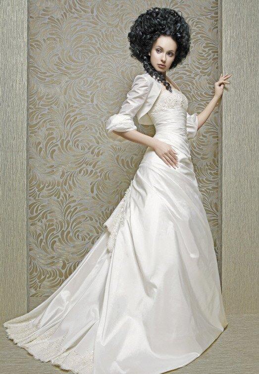 Фактурное свадебное платье с пышным шлейфом и болеро с плотным рукавом.