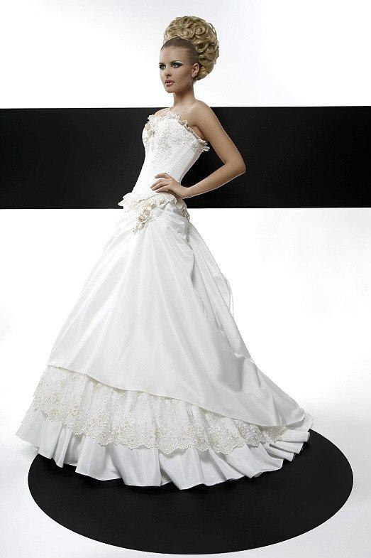 Свадебное платье с роскошным декором пышной юбки и открытым верхом.