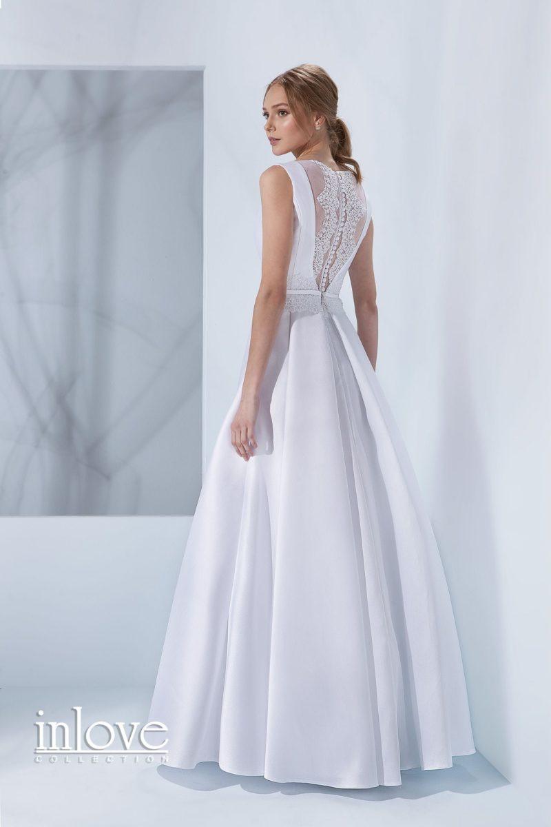 Атласное свадебное платье пышного кроя с оригинальным вырезом, украшенным кружевом, сзади.