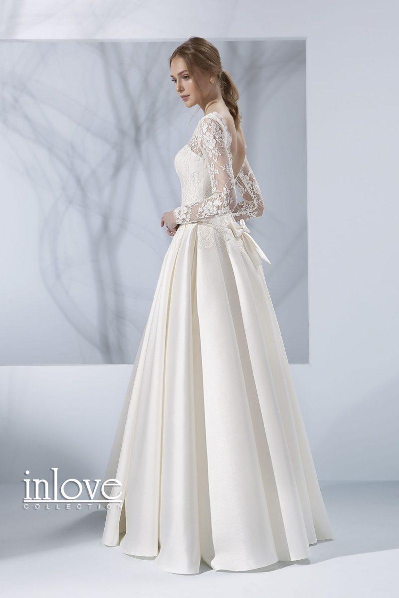 Атласное свадебное платье с открытой спинкой и длинными кружевными рукавами.