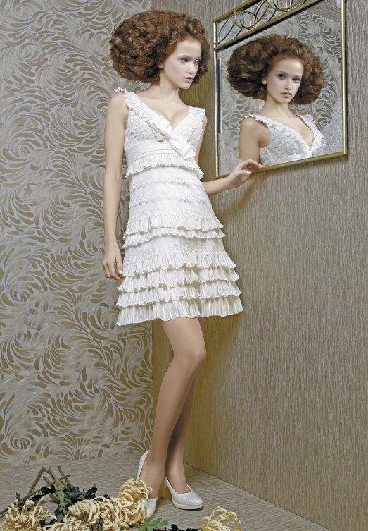 Короткое свадебное платье с множеством оборок и V-образным лифом.