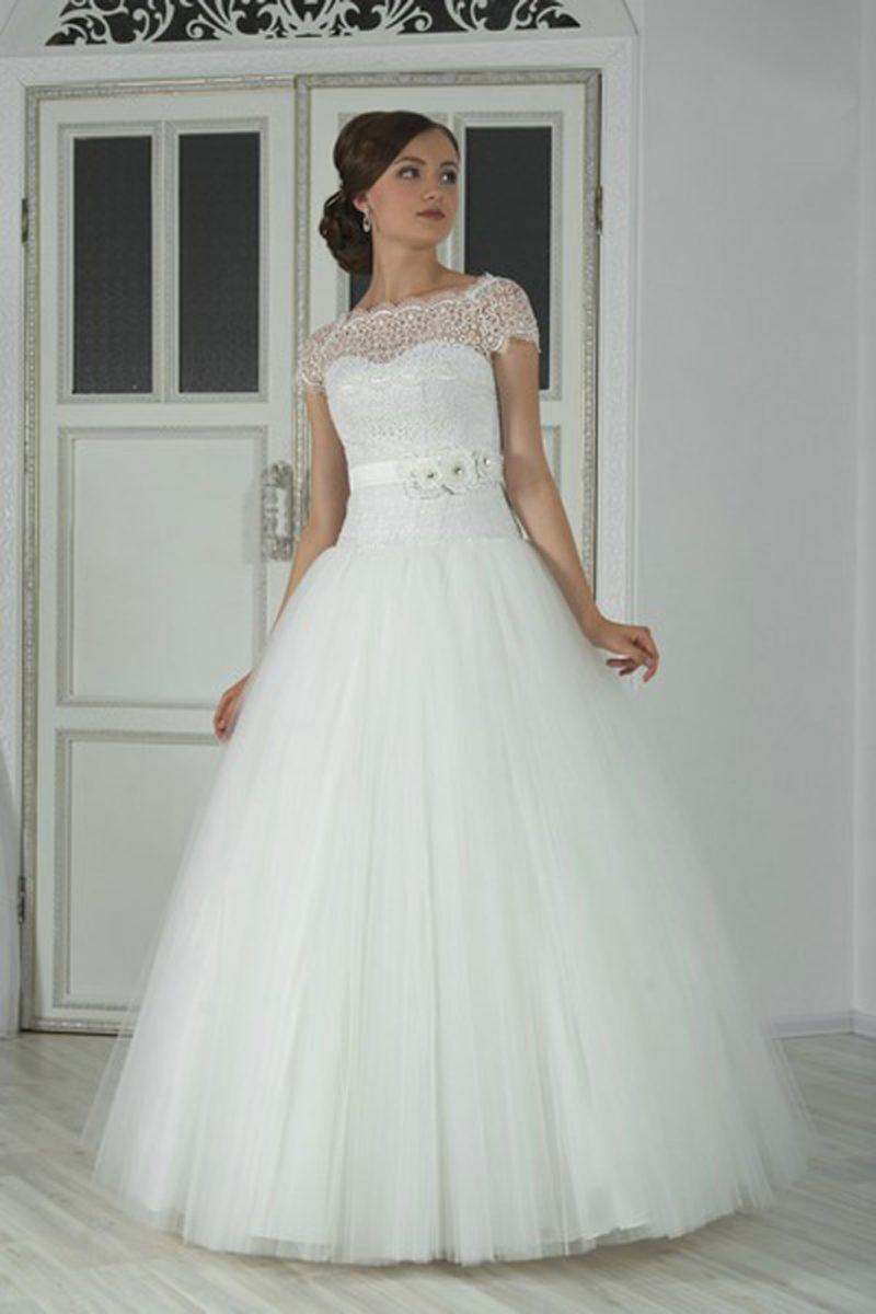 Пышное свадебное платье с фигурным кружевным вырезом, коротким рукавом и поясом с объемным бутоном сбоку.