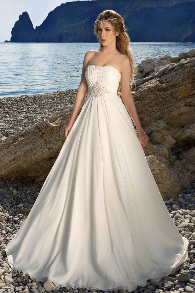 Открытое свадебное платье с лаконичным лифом и вышивкой на линии талии.