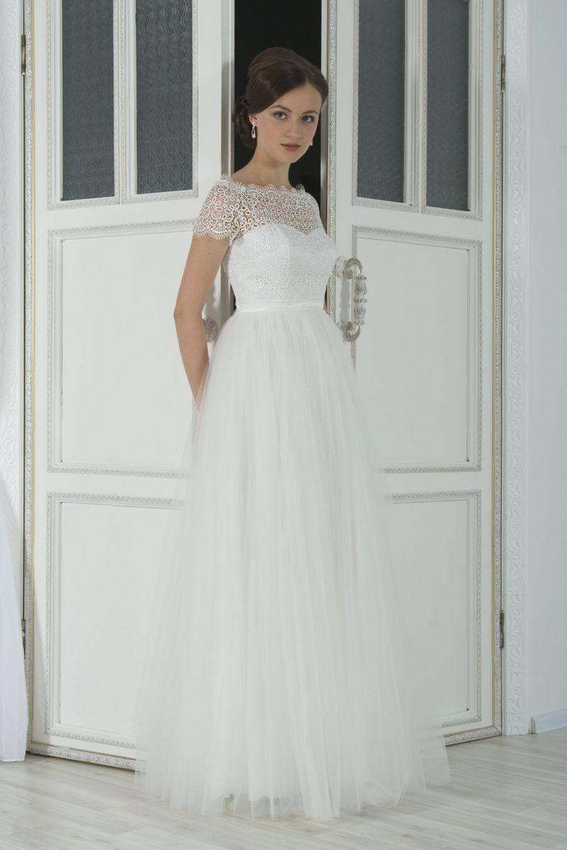 Романтичное свадебное платье с многослойной юбкой и кружевной отделкой верха.