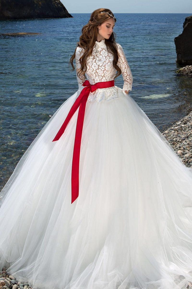 Пышное свадебное платье с высоким кружевным воротником и длинными облегающими рукавами.