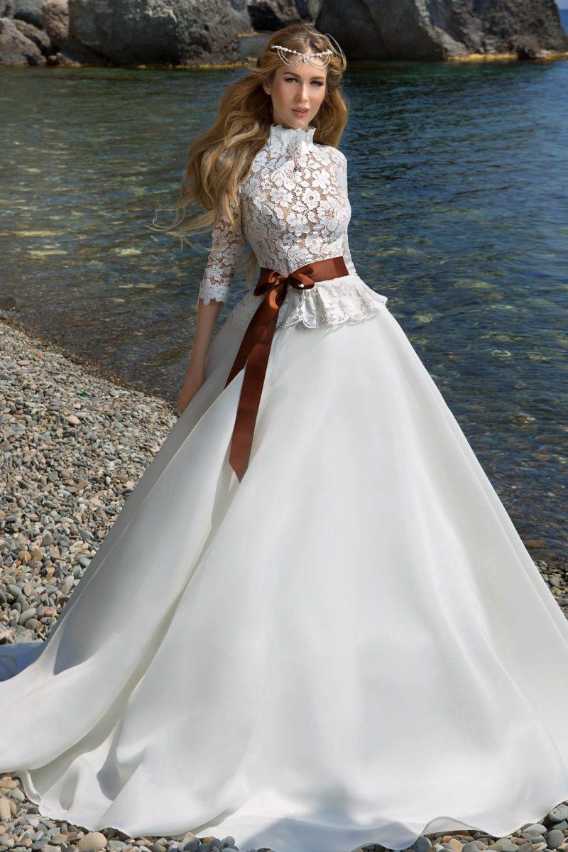 Роскошное свадебное платье с воротником-стойкой, длинными кружевными рукавами и пышным низом.