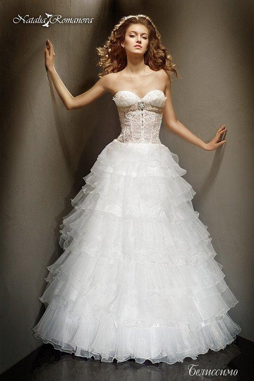 Свадебное платье с пастельного цвета подкладкой верха и пышной юбкой с тонкими оборками.