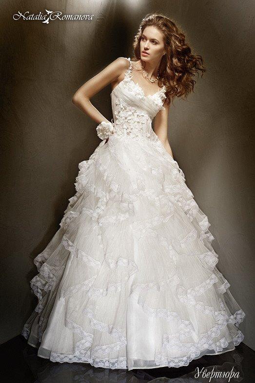 Свадебное платье с узкими бретелями, объемным декором корсета и оборками на юбке.