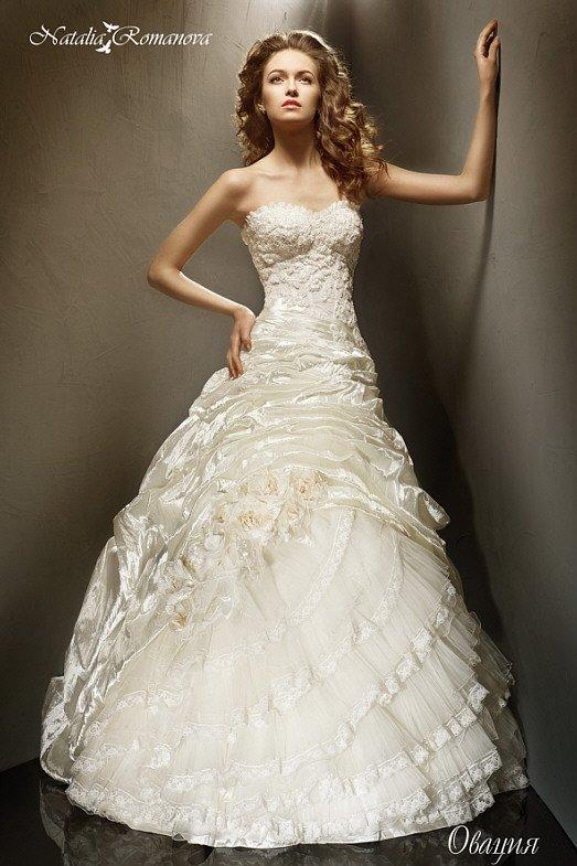 Свадебное платье с объемной отделкой облегающего корсета и многослойной юбкой.