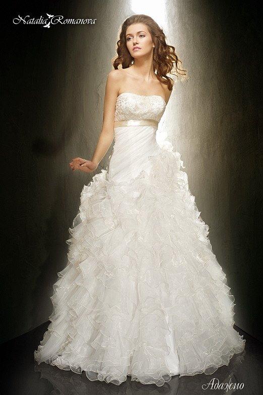 Свадебное платье с атласным поясом под открытым лифом и пышными оборками на юбке.