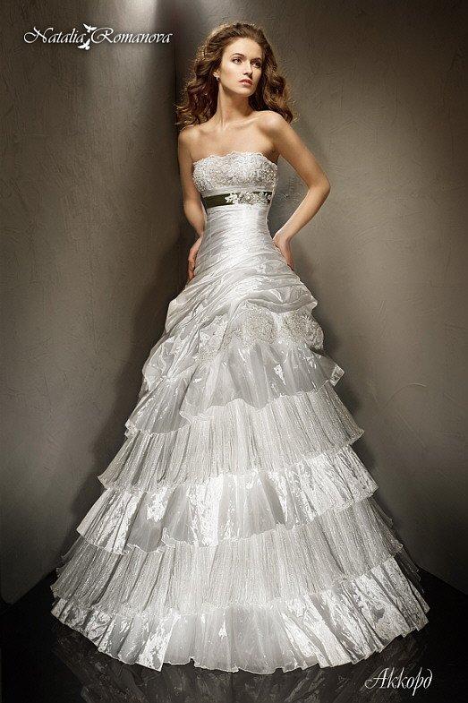 Свадебное платье с множеством ярусов ткани на пышной юбке и открытым лифом прямого кроя.