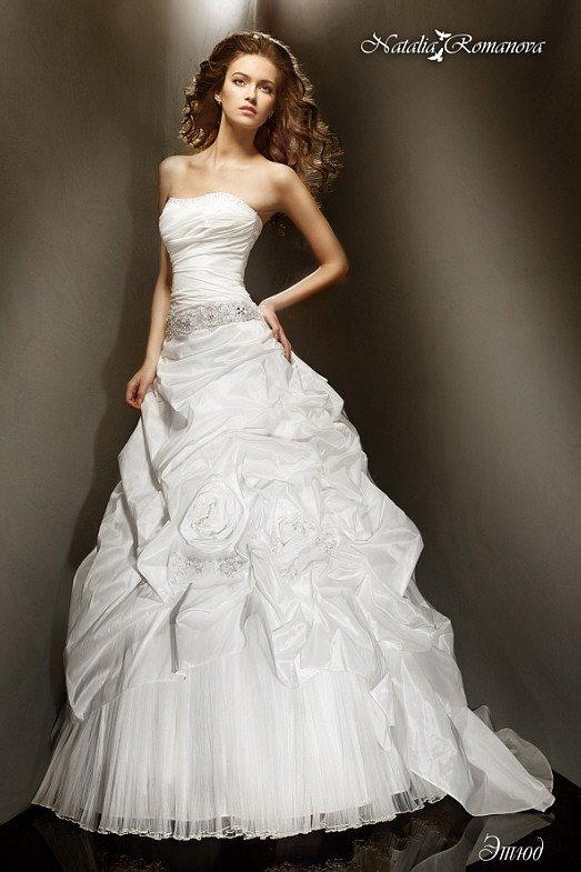 Запоминающееся свадебное платье с прямым вырезом и фактурными складками по пышной юбке со шлейфом.