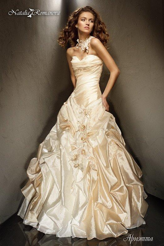 Кремовое свадебное платье пышного кроя с драпировками и пышными бутонами на юбке.