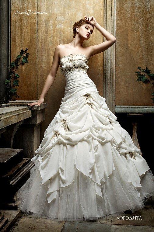 Роскошное свадебное платье с прямой линией декольте и пышными волнами ткани на юбке.