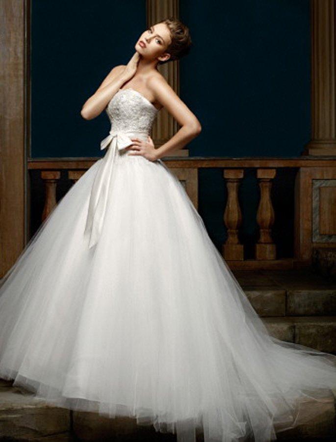 Романтичное свадебное платье со сдержанным открытым корсетом и широким поясом с бантом.