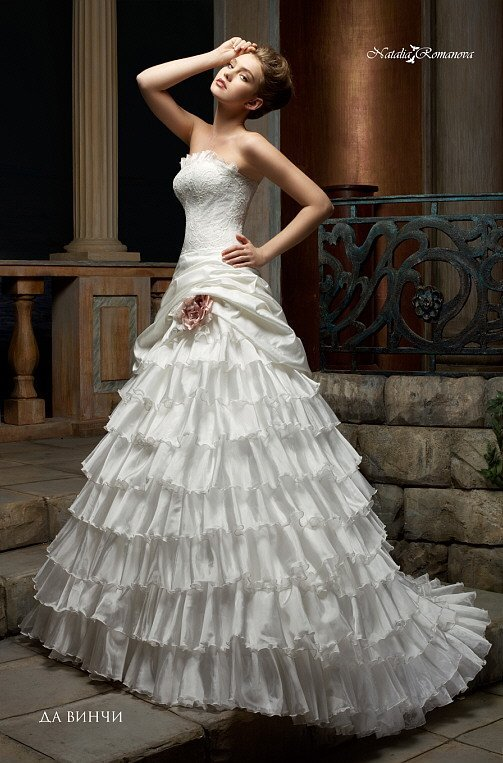 Свадебное платье с оборками по лифу прямого кроя и воланами на юбке с длинным шлейфом.