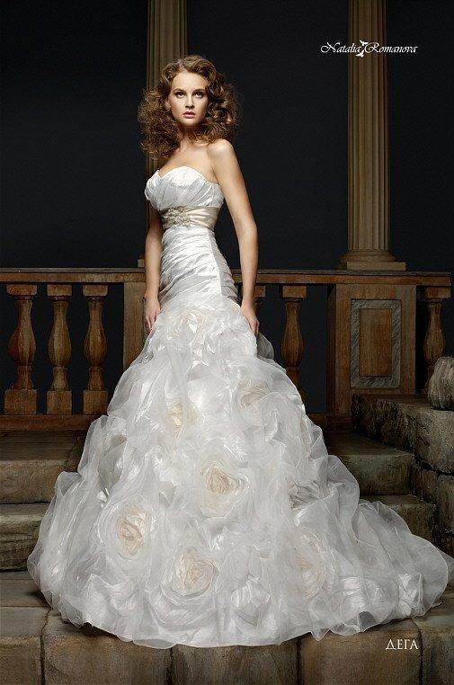 Роскошное свадебное платье с открытым декольте и пышными бутонами по низу подола.