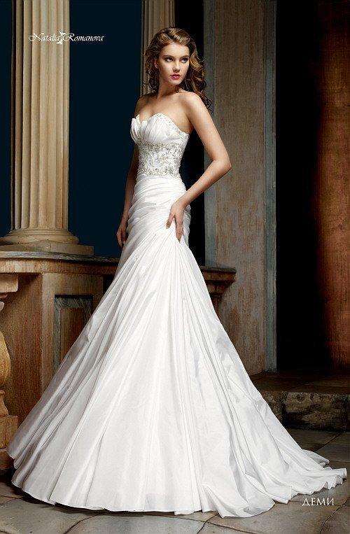 Свадебное платье «принцесса» с украшенной драпировками юбкой и выразительным декольте.