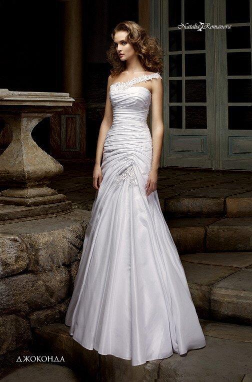 Атласное свадебное платье с асимметричным лифом и роскошными складками ткани.