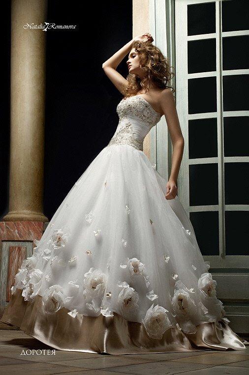 Незабываемое свадебное платье пышного кроя с золотистым атласом и бутонами по низу подола.