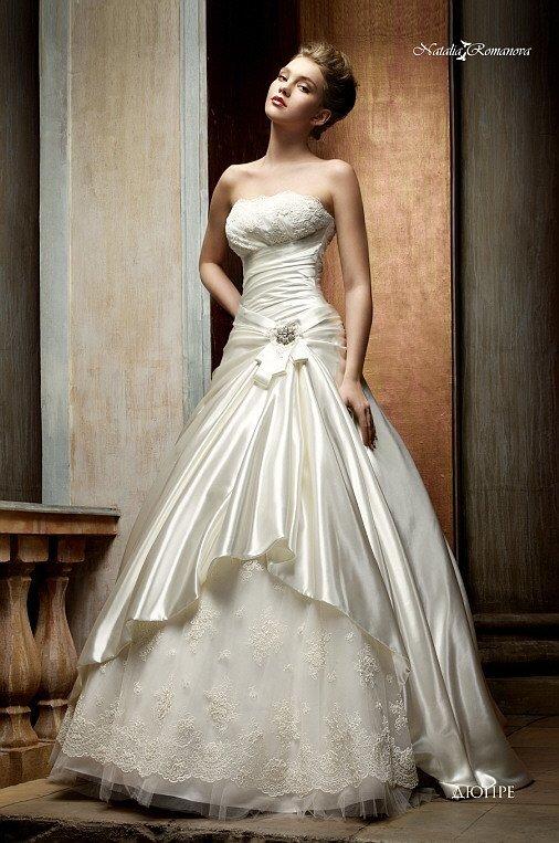 Открытое свадебное платье с атласной юбкой пышного кроя и стильными драпировками.