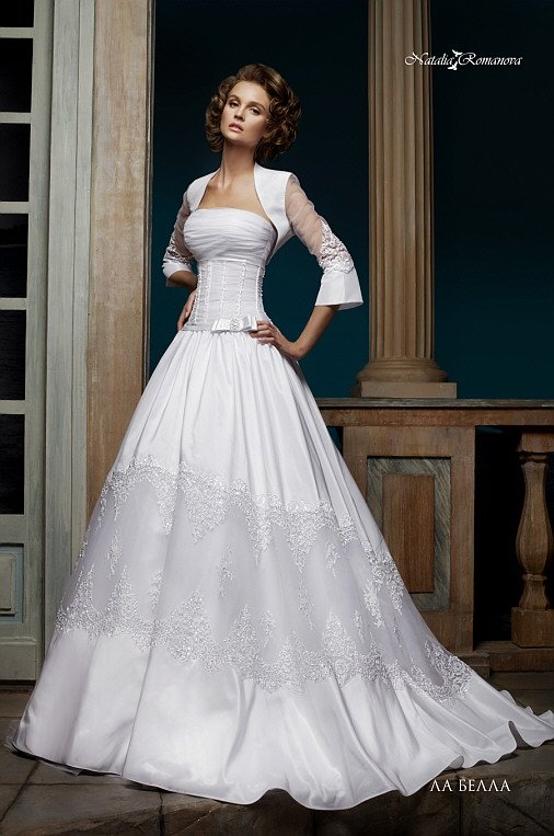 Элегантное свадебное платье пышного кроя с атласным болеро и кружевными вставками по подолу.