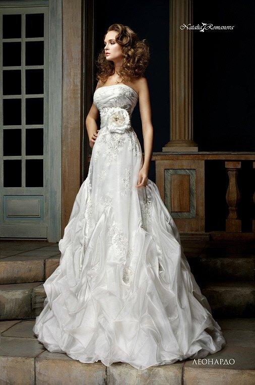 Открытое свадебное платье с крупным бутоном на талии и роскошной отделкой низа подола.