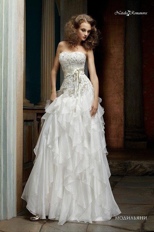 Фактурное свадебное платье с открытым лифом и юбкой «принцесса», покрытой оборками.