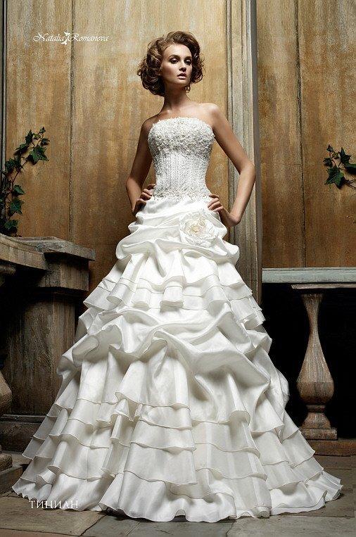 Открытое свадебное платье с лифом прямого кроя и роскошной юбкой с глянцевыми оборками.